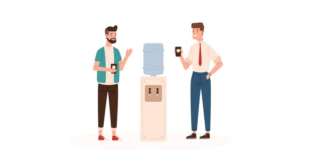 Colleagues talking around water cooler